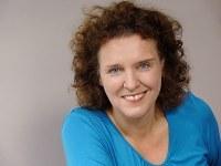 lächelnde Frau vor dunkelgrauem Hintergrund. Brünette, schulterlange, gelockte Haare und blaues Oberteil